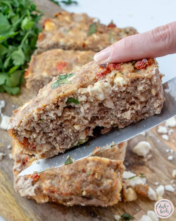 An image of the feta and sundried tomato turkey meatloaf recipe. The meatloaf is sliced and one of the slices is the focal point raised on the knife that cut it. There is fresh parsley in the background.
