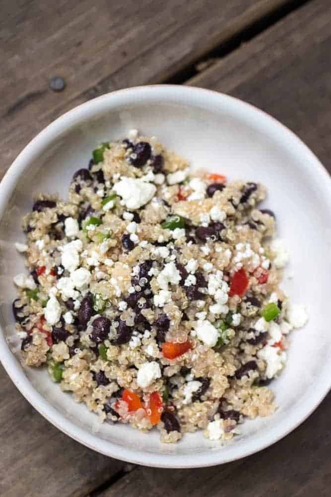 An overhead image of the Healthy Black Bean Quinoa Salad with Feta recipe in a white bowl.  You can see the quinoa, black beans, peppers and feta cheese in the image.