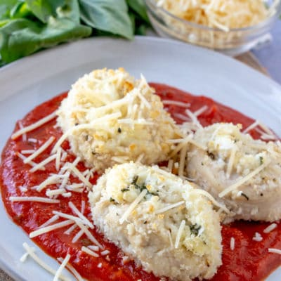 Chicken Parmesan Rollups laying on marinara and sprinkled with parmesan.