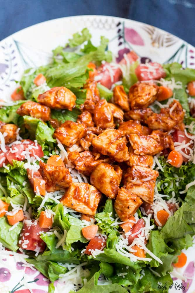 A close up image of the BBQ Chicken Salad recipe on a colorful plate.  You can see the BBQ chicken, carrots, romaine lettuce, tomatoes and cheese.
