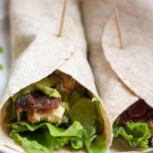 An image of the California Chicken Wrap recipe that is on a white plate. The image has two wraps with grilled chicken, avocado spread, bacon and lettuce.
