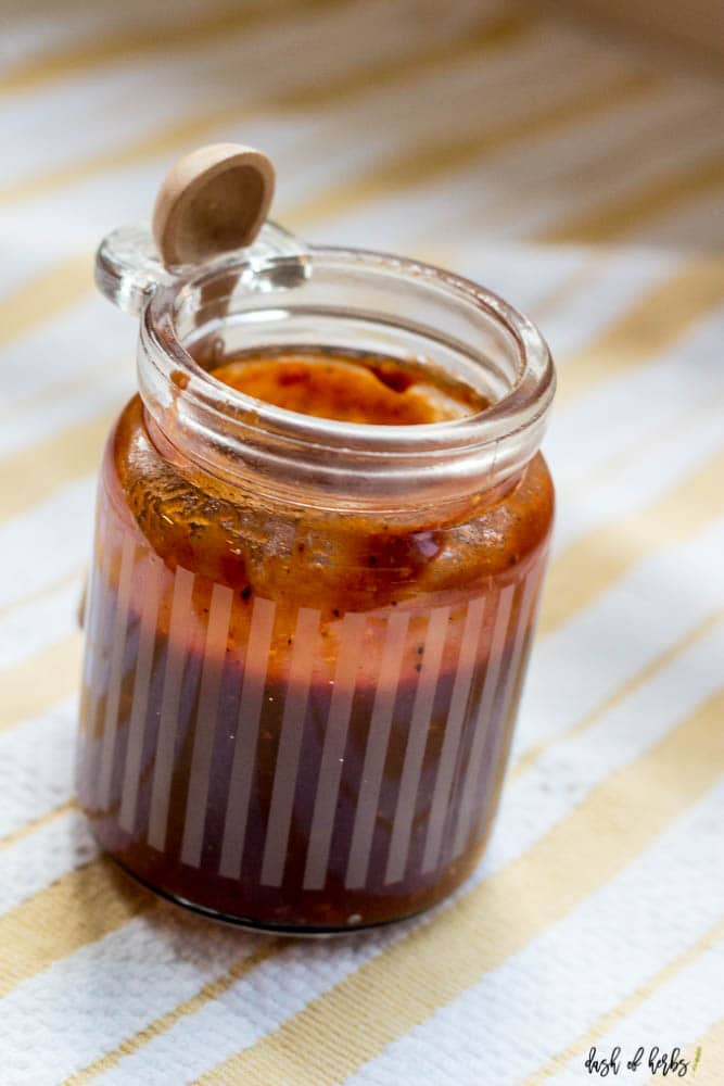 A close up image of the Homemade BBQ Sauce in a small clear jar.  There is a small wooden spoon hooked onto the clear jar.  A yellow and white striped cloth napkin is underneath the clear jar.