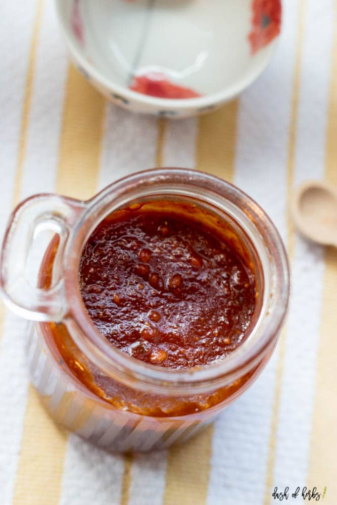 An overhead image of the Homemade BBQ Sauce in a small clear jar.  There is a small wooden spoon and small decorative bowl in the background.  A yellow and white striped cloth napkin is underneath the clear jar.