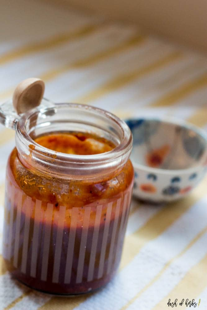 A close up image of the Homemade BBQ Sauce in a small clear jar.  There is a small wooden spoon and small decorative bowl in the background.  A yellow and white striped cloth napkin is underneath the clear jar.