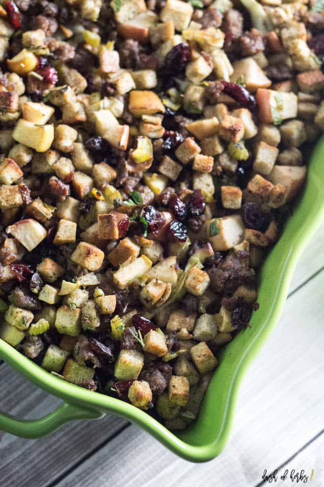 An overhead image of the Apple Sausage Cranberry Stuffing recipe in a green colorful ceramic pan.  You can see the dried cranberries, apples, stuffing and sausage in the image.