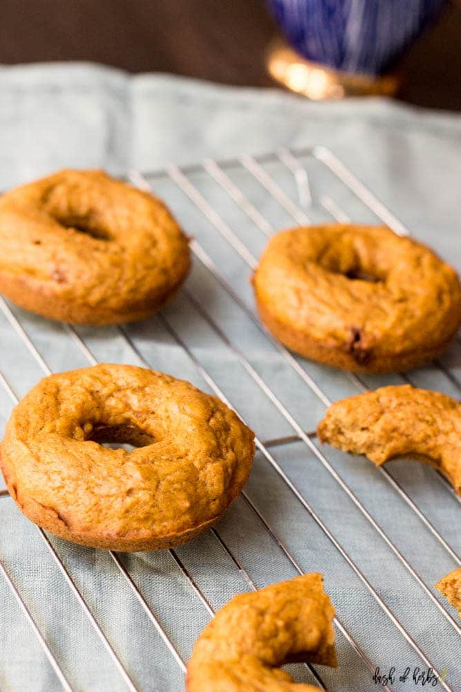 An overhead image of the Healthy Baked Pumpkin Spice Donuts on a cooling rack.  There are three donuts with one broken apart in the image.