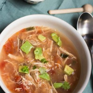 An overhead image of the Slow Cooker Chicken Tortilla Soup recipe in a white bowl. You can see a light blue napkin underneath the bowl. There is a decorative small bowl in the background.