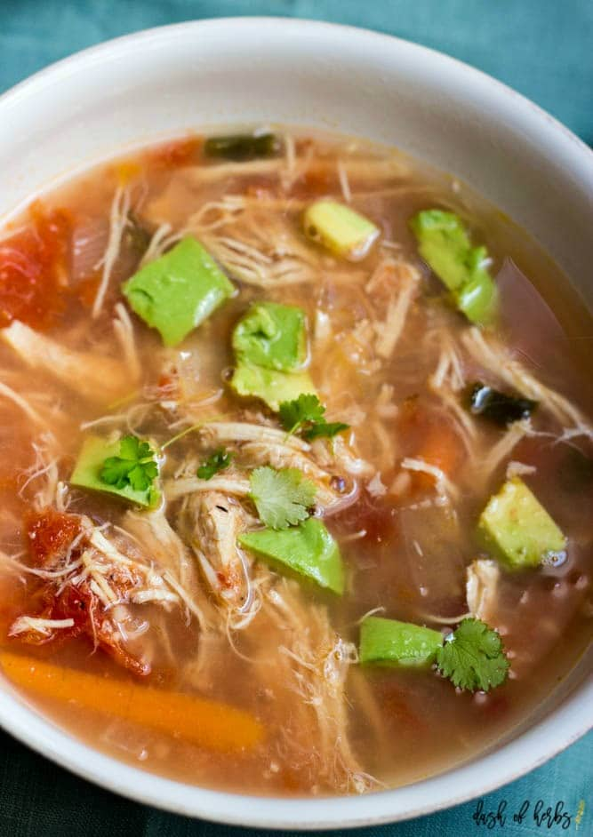 An close up image of the Slow Cooker Chicken Tortilla Soup recipe in a white bowl.  You can see a light blue napkin underneath the bowl.  You can see the shredded chicken, tomatoes, corn, black beans and chopped avocado in the image.