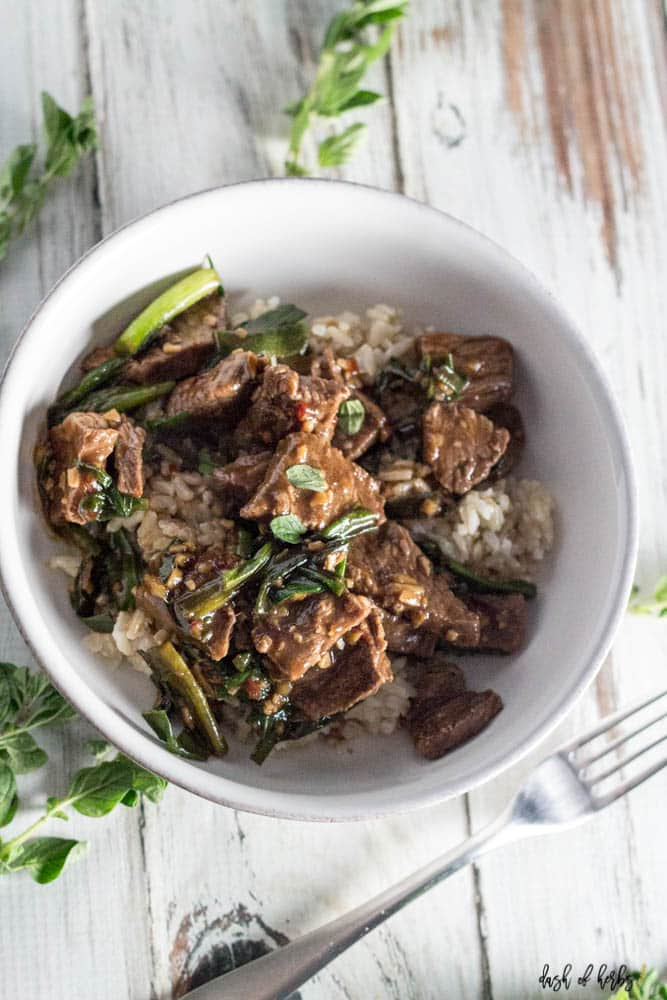 An overhead image of the Skillet Mongolian Beef recipe.  You can see the beef, green onions and rice all in a white bowl.  There is also a fork next to the bowl.