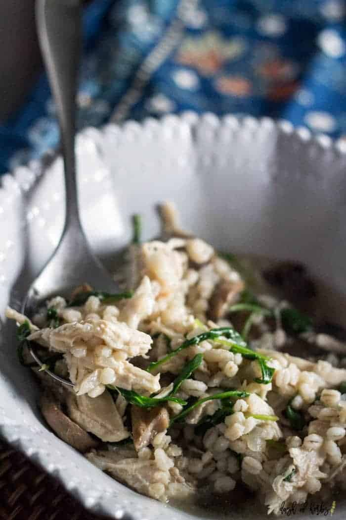 An image of the Barley and Chicken Risotto recipe in a light grey decorative bowl. There is a spoon in the risotto and a decorative napkin in the background.