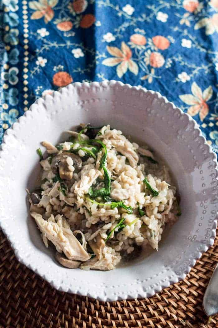 An overhead image of the Barley and Chicken Risotto recipe in a light grey decorative bowl. There is a spoon in the risotto and a decorative floral napkin in the background.