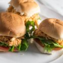 An close up image of the slow cooker Buffalo Chicken Sliders on a white plate. There are 3 sliders on the plate and each slider has lettuce and tomato along with the buffalo chicken.
