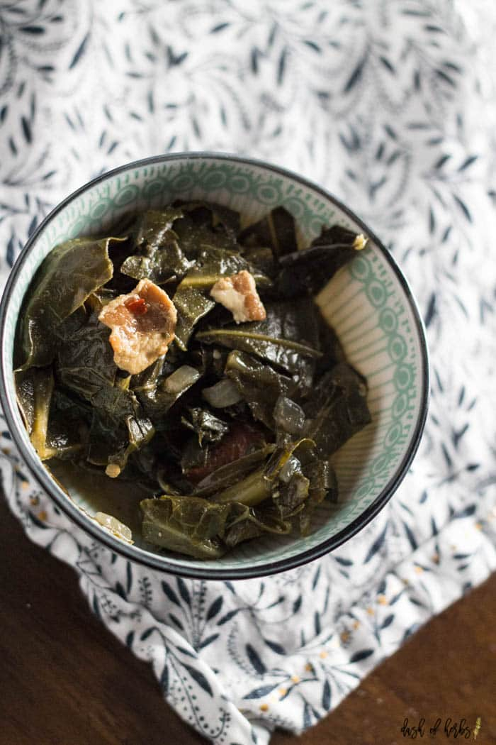 An overhead image of the One Pot Southern Collard Greens recipe that shows the collar greens in a decorate blue bowl.  You can see a white and navy napkin underneath the bowl.