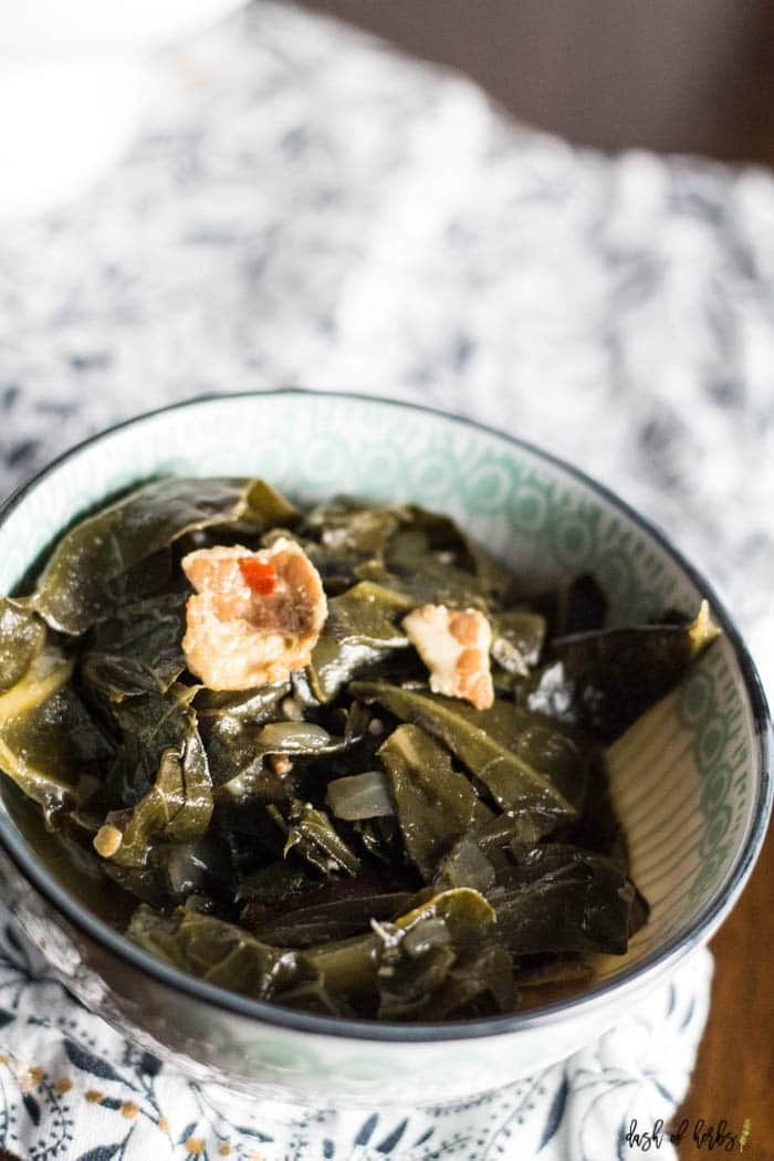 A close up image of the One Pot Southern Collard Greens recipe that shows the collar greens in a decorate blue bowl.  You can see a white and navy napkin underneath the bowl.