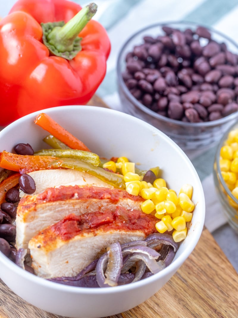 Bowl with sheet pan chicken fajita bowls with corn, black beans and red onions. A large red pepper is in the background of the image.