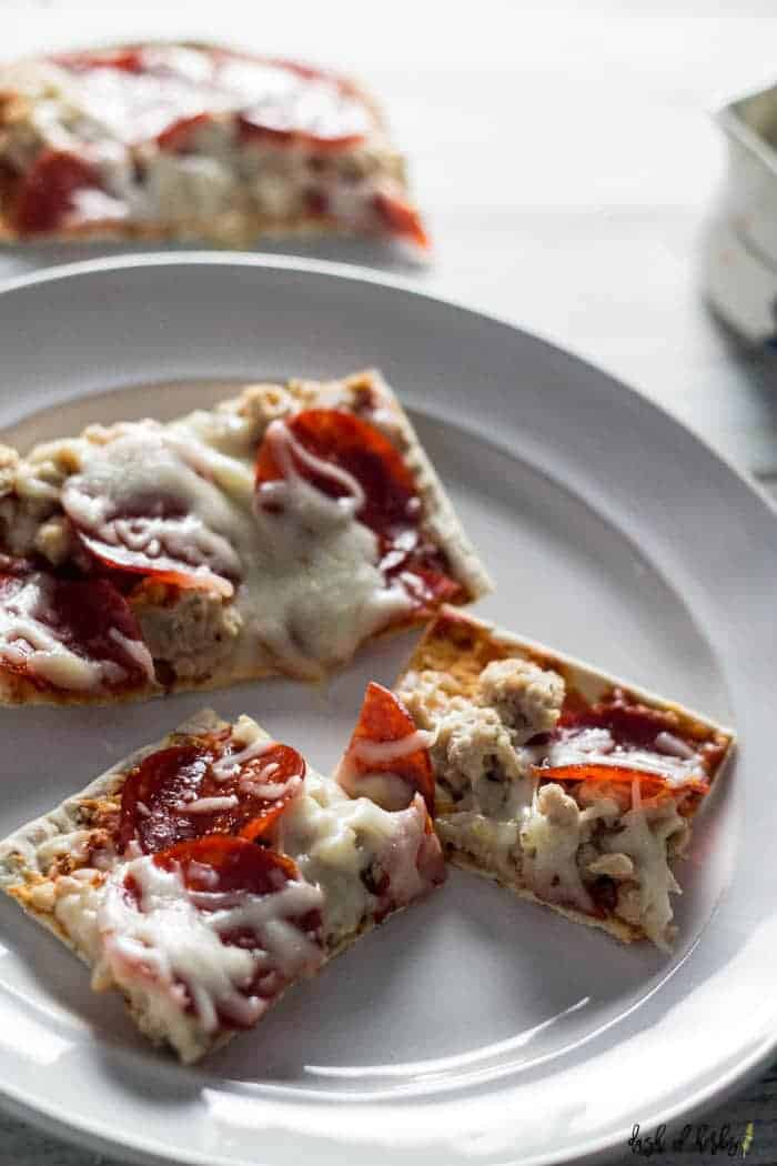 An image of the Chicken and Turkey Pepperoni Pizza recipe on a white plate.  There are three slices of the pizza in the picture.  You can see the rest of the pizza in the background.