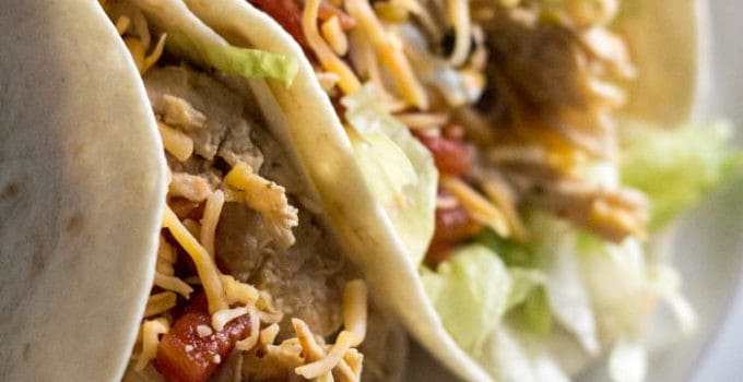 A close up image of the Instant Pot Chipotle Chicken Tacos recipe. There are two tacos shows with lettuce, chipotle chicken and cheese. The tacos are on a bright white plate ready to eat.