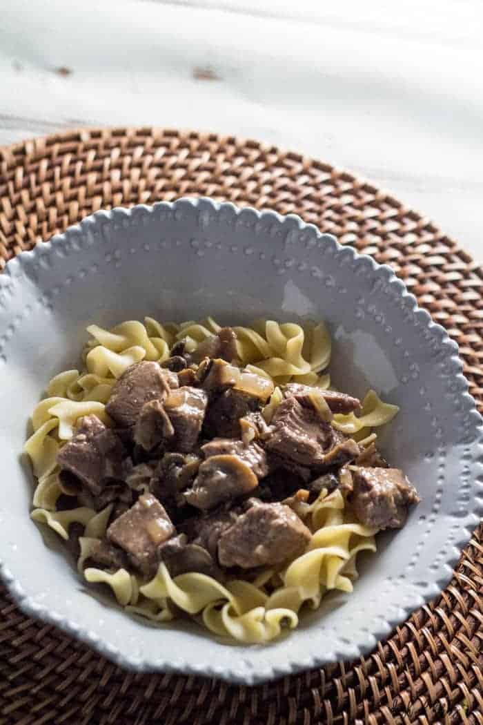 An overhead image of the Slow Cooker Beef Stroganoff recipe. This recipe is in a light grey decorative bowl which is sitting on a charger.
