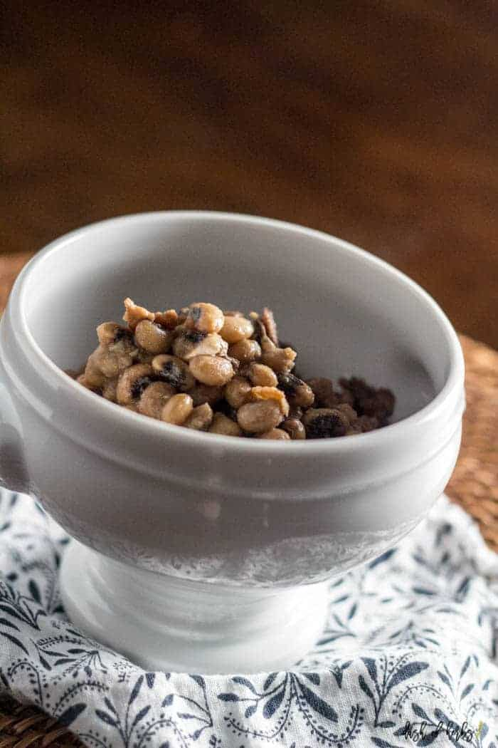 A close up image of the Slow Cooker Black Eyed Peas recipe in a white display bowl.  The bowl is on top of a navy blue and white decorative napkin.