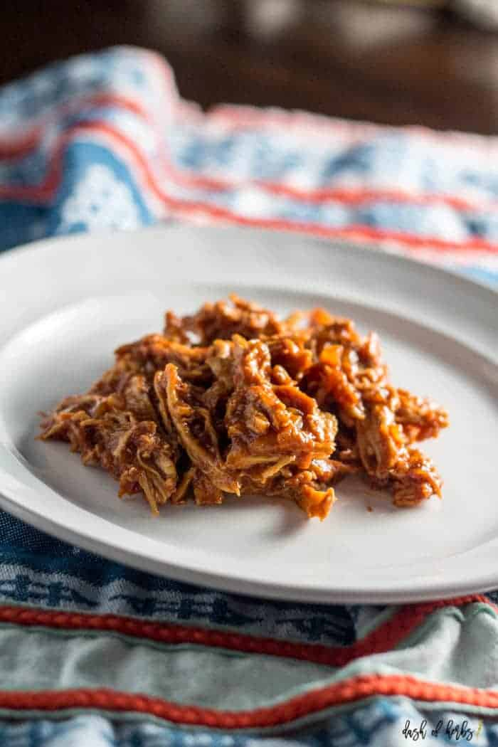 A close up image of the Slow Cooker Pulled BBQ Chicken recipe.  The pulled chicken is on a white plate with a colorful napkin underneath the plate.