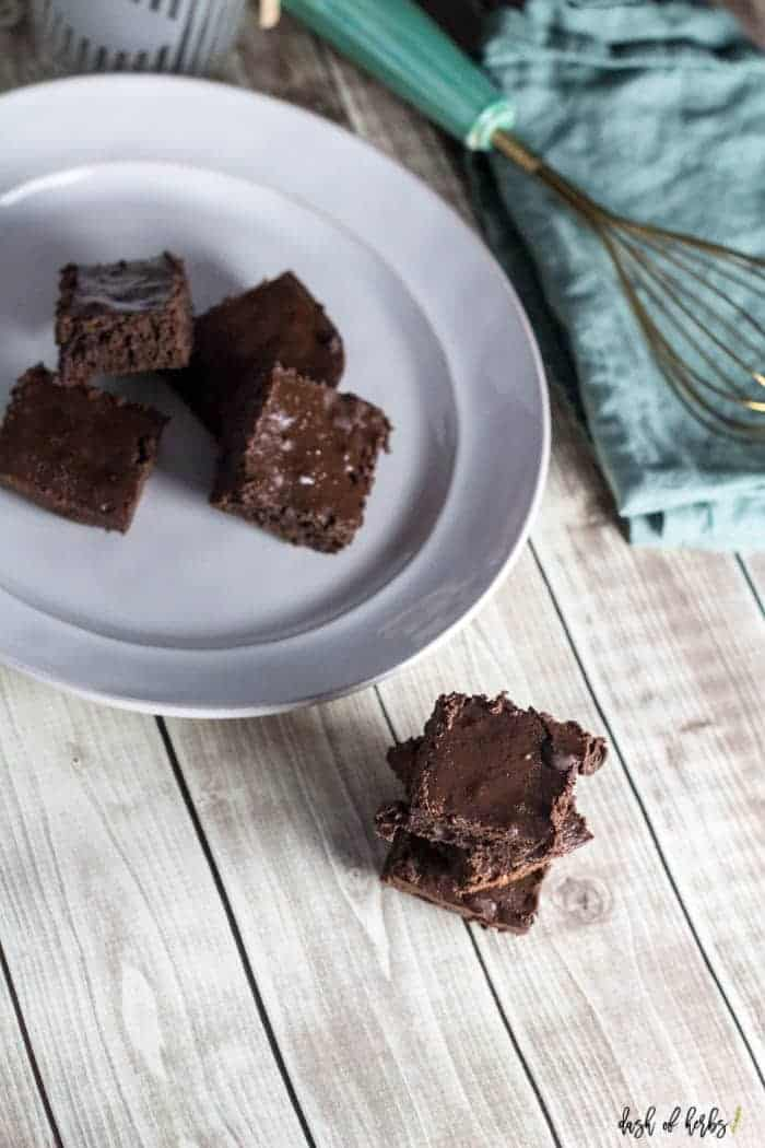 An overhead image of the Chocolate Chip Fudge Brownies recipe.  The chocolate chip brownies are cut and stacked on top of each other.  You can see a white plate with a few brownies on it in the background.