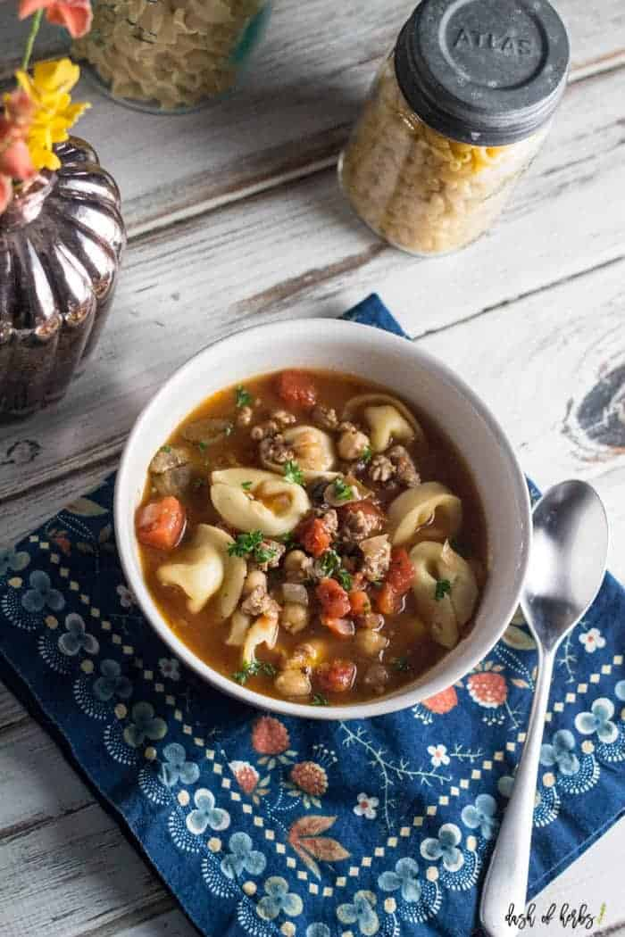 An overhead image of the Hearty Tortellini Soup with Sausage in a white bowl.  There is a very colorful napkin underneath  the bowl and flowers are in the corner of the image.