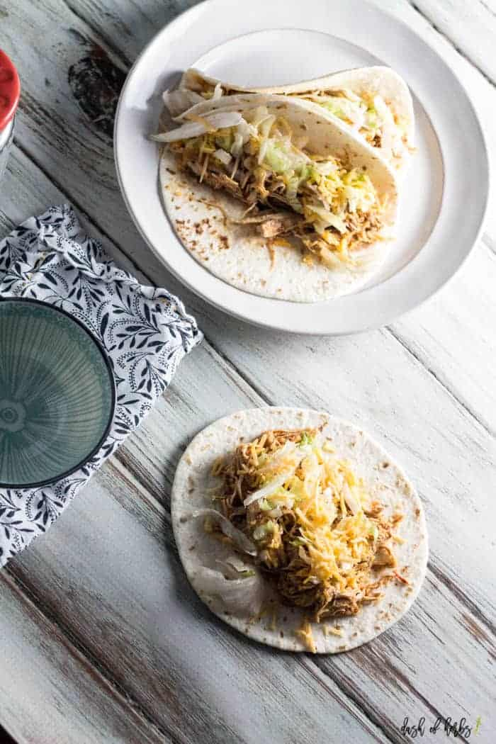 An image of the Instant Pot Easy Chicken Tacos recipe.  There is one taco in the front of the picture, and 2 tacos together on a plate behind it.  There is an empty bowl and navy blue napkin in the image as well.