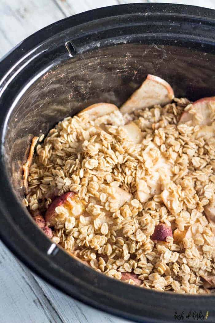 An image of the slow cooker apple peach crumble recipe showing the slow cooker. You can see the oats and the sliced apples beautifully in this image.