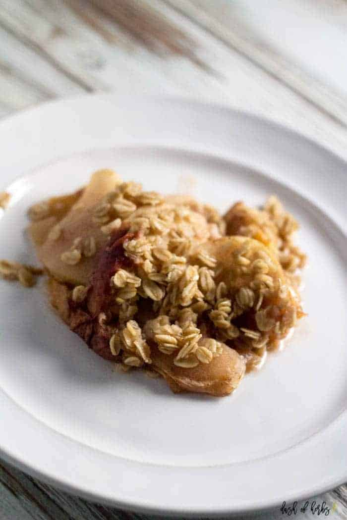 An image of the slow cooker apple peach crumble recipe. A spoonful of the dessert is on a white plate showing the peach chunks and oats.