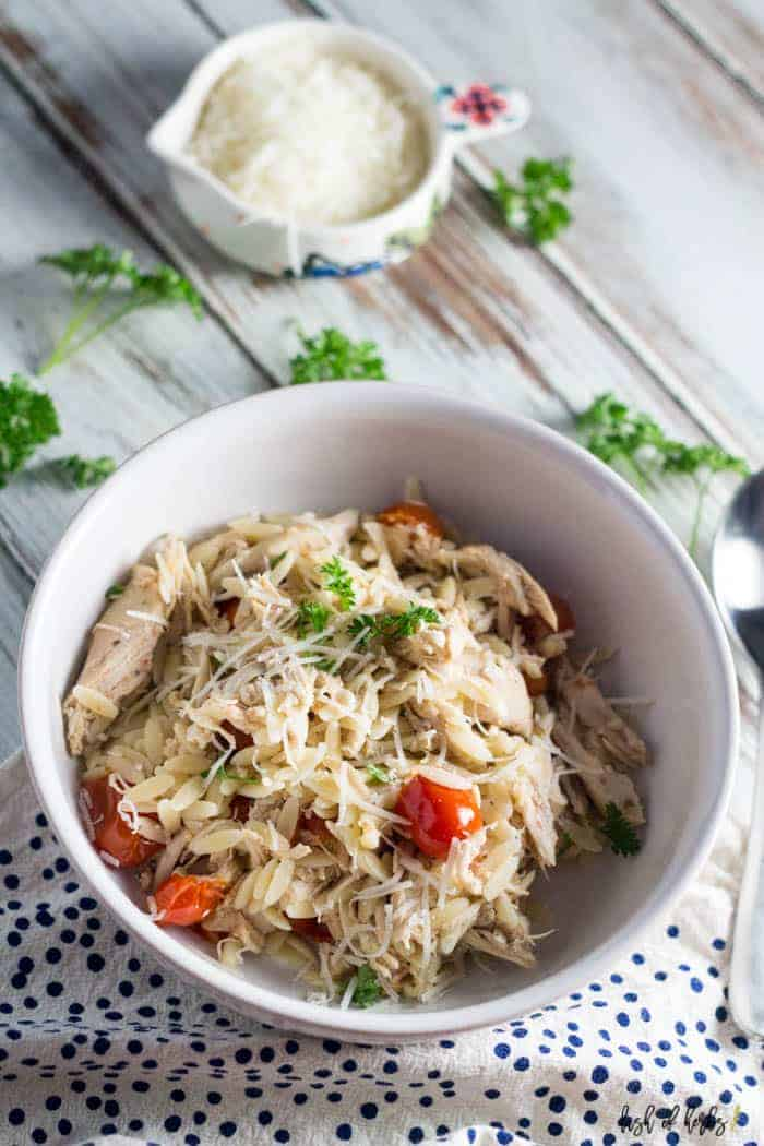 An overhead image of the Slow Cooker Chicken and Tomato Orzo recipe. You can see the shredded chicken, tomatoes and orzo in the image. There is a small bowl in the background filled with Parmesan cheese.