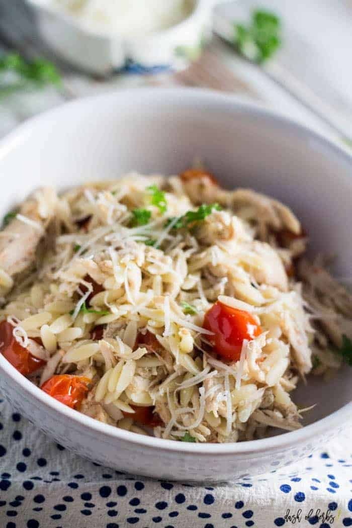 An close up image of the slow cooker chicken and tomato orzo recipe.  The grape tomatoes and orzo are on display in this image.  Shredded Parmesan cheese is in a small colorful bowl in the background.