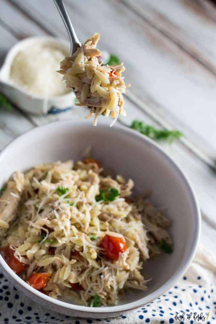 An image of the slow cooker chicken and tomato orzo recipe.  There is a bite of the meal on a fork which is front an center.  Shredded Parmesan cheese is in a small colorful bowl in the background.