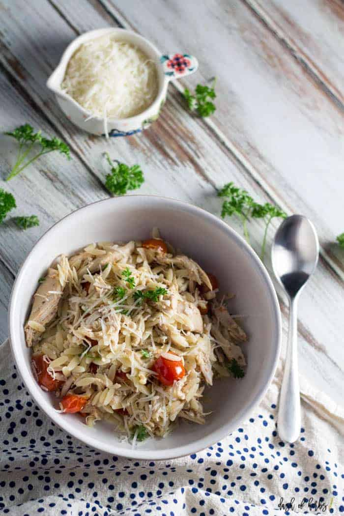 An overhead image of the slow cooker chicken and tomato orzo recipe.  Shredded Parmesan cheese is in a small colorful bowl in the background.