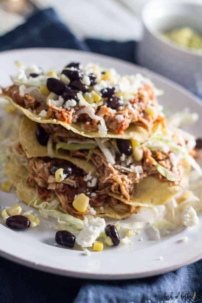 An image of the Slow Cooker Salsa Chicken Tostadas recipes on a white plate.  There are 3 tostadas stacked on top of each other with black beans, corn and lettuce on the plate.  There is a navy blue napkin underneath the plate.  There is a small bowl of guacamole in the background.