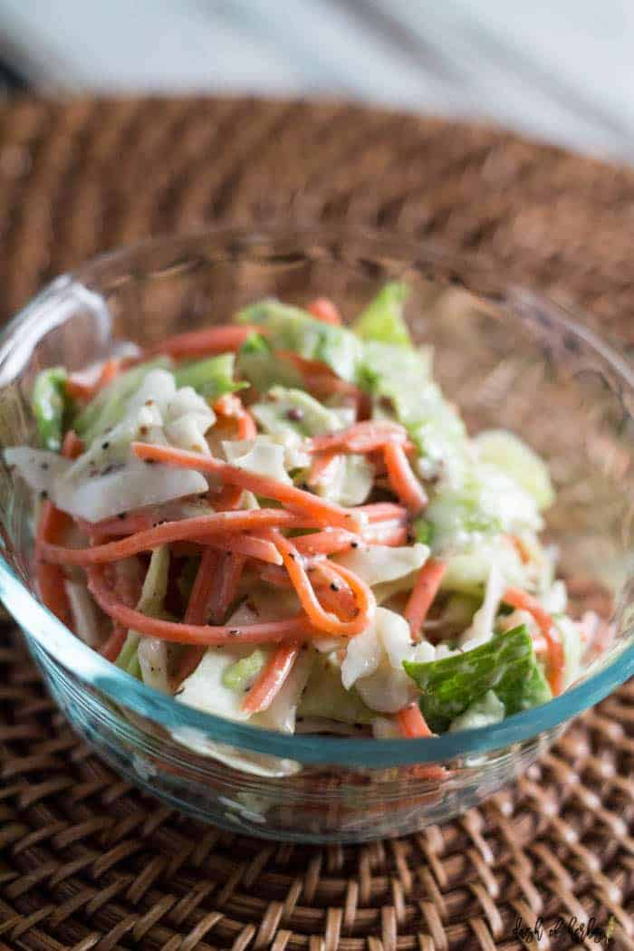 A close up image of the Spicy Creamy Coleslaw recipe is in a clear bowl.  The bowl is on a brown rattan charger.
