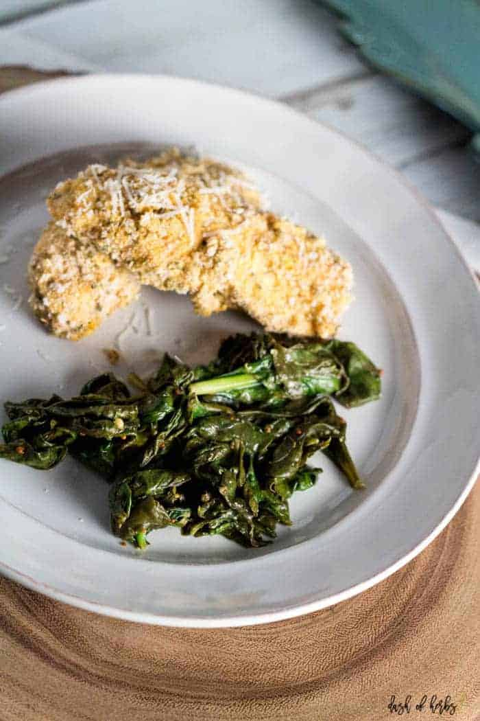 An image of the baked cornmeal chicken and greens recipe on a white plate.  The image has one chicken breast with the cooked greens.