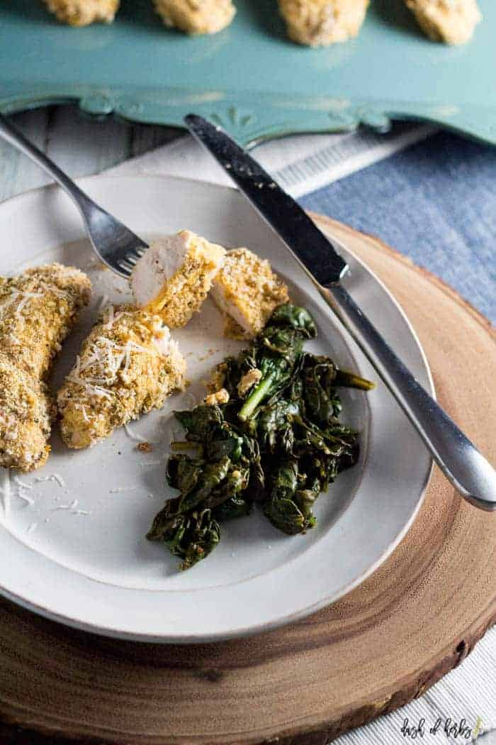 An image of the baked cornmeal chicken and greens recipe on a white plate.  The image has one chicken breast ready to eat with a fork and knife with the cooked greens.
