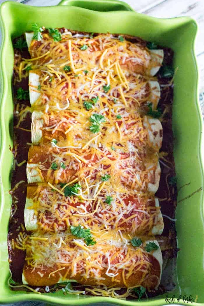 An overhead image of the Instant Pot Chicken Enchiladas recipe with 8 enchiladas in a pan. The pan is a ceramic light green pan.