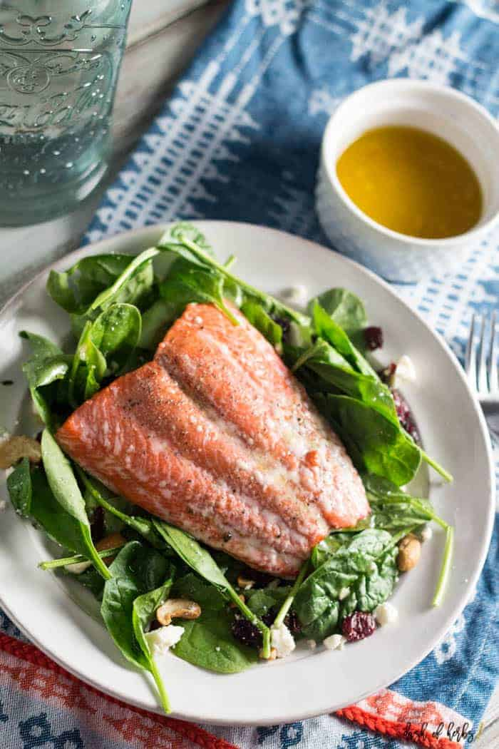 An image of the Simple Salmon Summer Salad recipe with a small bowl of the dressing in the upper righthand corner.  There is a decorative blue napkin underneath the recipe and dressing.