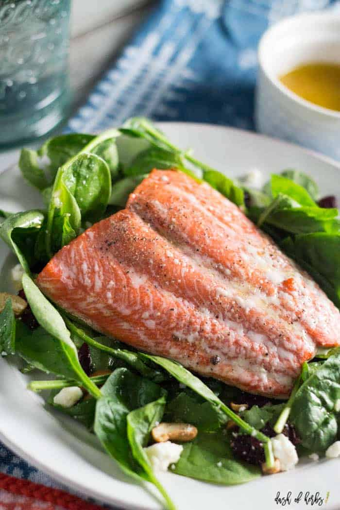 A close up image of the Simple Salmon Summer Salad recipe with a small bowl of the dressing in the upper righthand corner.  There is a decorative blue napkin underneath the recipe and dressing.