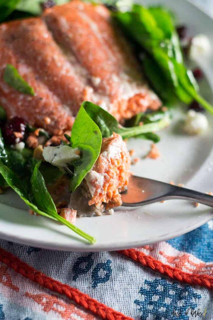 An image of the Simple Salmon Summer Salad recipe with a small piece of salon and salad on a fork.  There is a decorative blue napkin underneath the recipe and dressing.