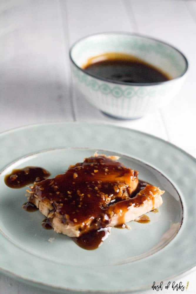 A photo of salmon covered in the easy healthy teriyaki sauce recipe on a small light blue plate.  There is more teriyaki sauce in a small bowl in the background