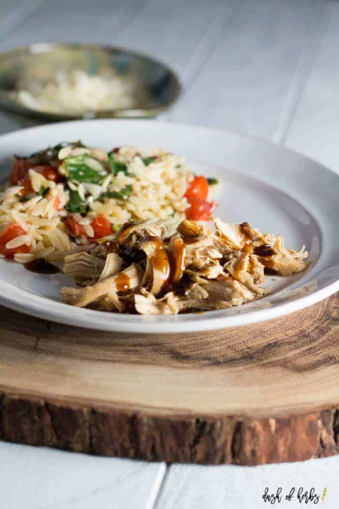 A photo of slow cooker teriyaki chicken with tomato orzo salad on a white plate.  The plate is on a large piece of cut wood.