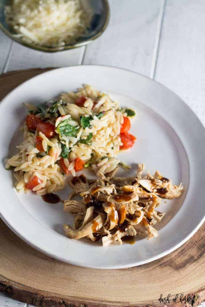 An overhead photo of slow cooker teriyaki chicken with tomato orzo salad on a white plate.  The plate is on a large piece of cut wood.  There is also a small bowl full of shredded cheese.