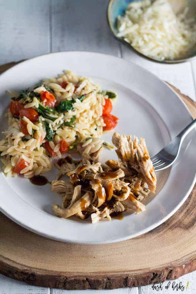 An overhead photo of slow cooker teriyaki chicken with tomato orzo salad on a white plate.  There is a bite of teriyaki chicken on a fork.  The plate is on a large piece of cut wood.  There is also a small bowl full of shredded cheese.