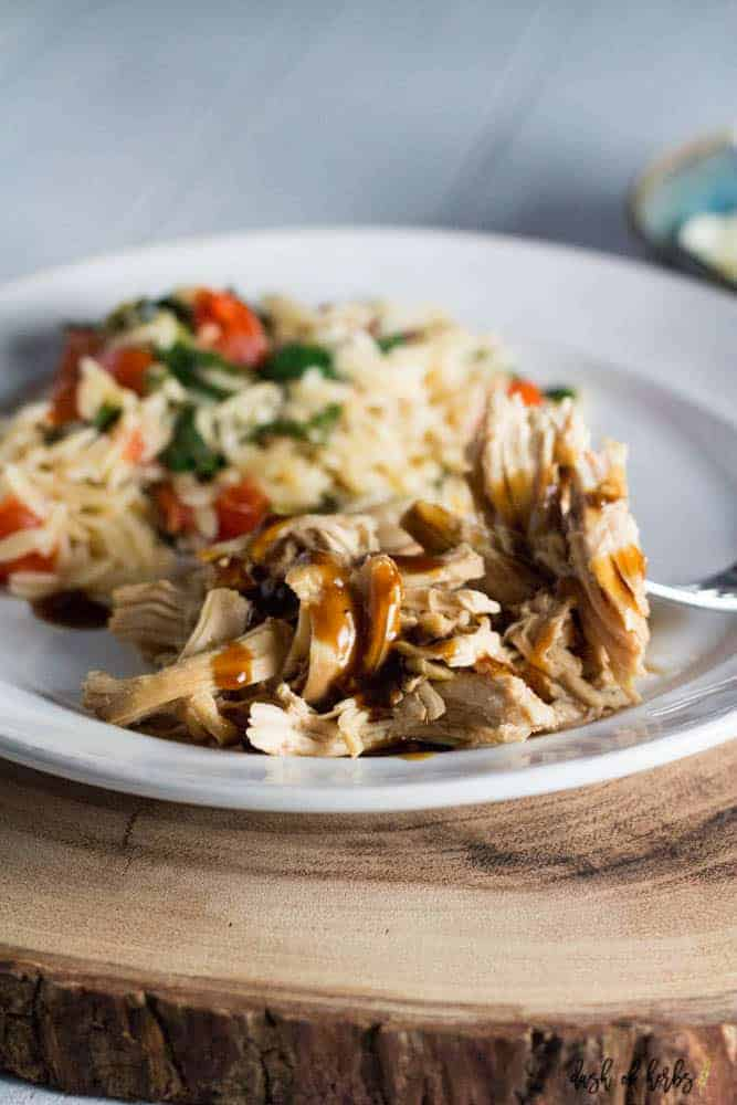 A close up photo of slow cooker teriyaki chicken with tomato orzo salad on a white plate.  The plate is on a large piece of cut wood.  There is a piece of teriyaki chicken on a fork ready for a bite. There is also a small bowl full of shredded cheese.
