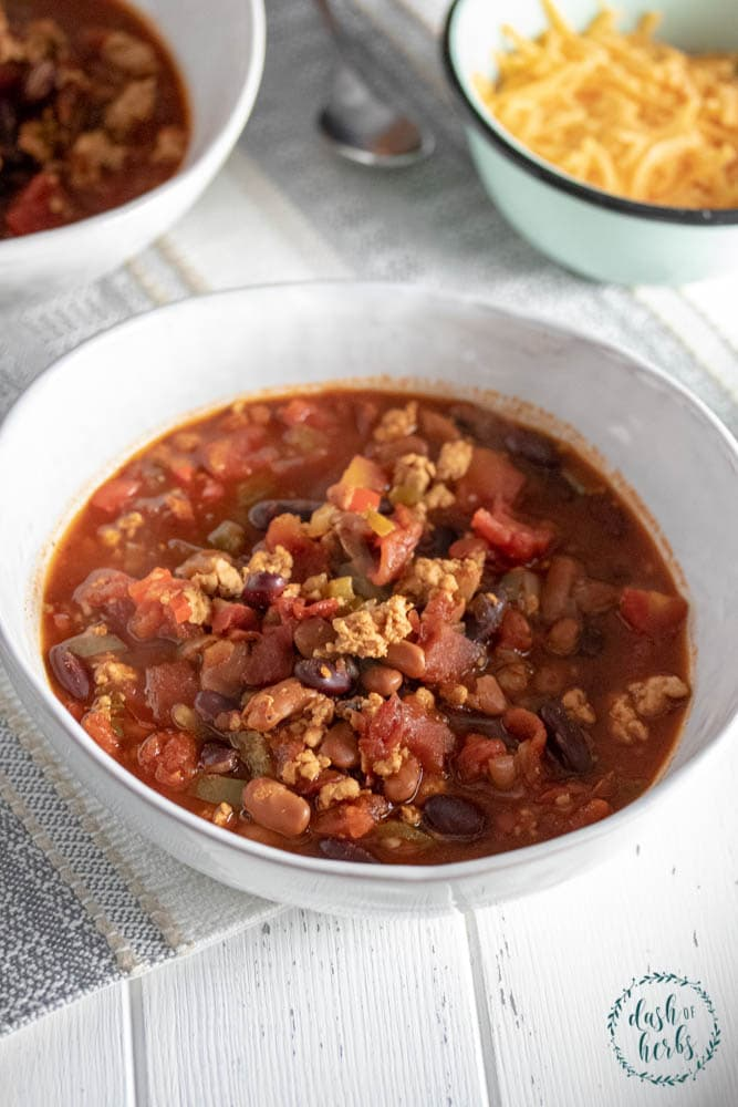 A close up photo of a bowl of Instant Pot Turkey Chili. A side of shredded cheese is in the upper righthand corner with another bowl of instant pot turkey chili in the background.