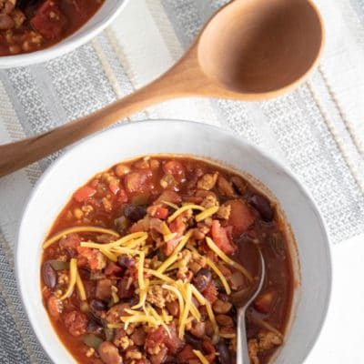 An overhead photo of a bowl of Instant Pot Turkey Chili with cheese. A side of shredded cheese is in the upper righthand corner with another bowl of instant pot turkey chili in the background.