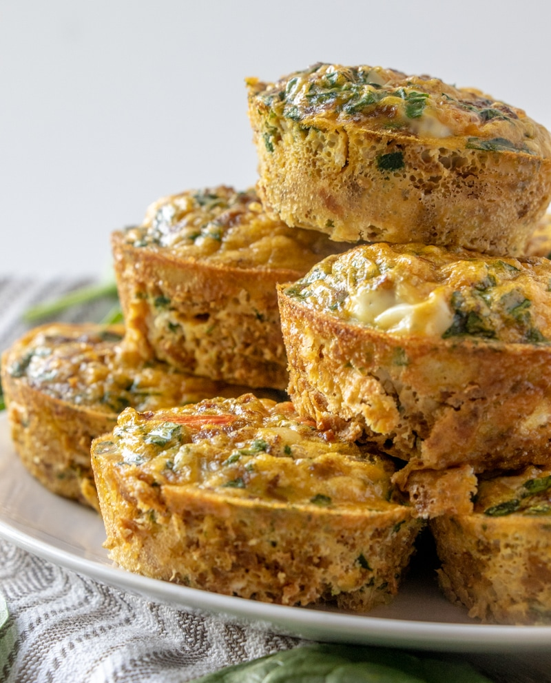 The turkey sausage and spinach mini quiches stacked on a plate.